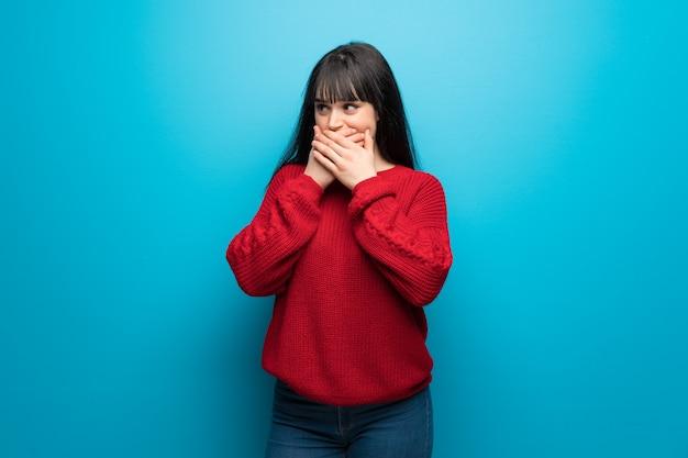 Donna con maglione rosso oltre la parete blu che copre la bocca e guardando al lato
