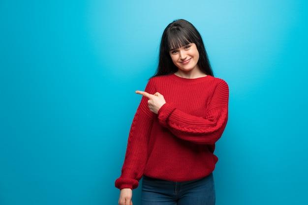 Donna con maglione rosso sulla parete blu che punta al lato per presentare un prodotto