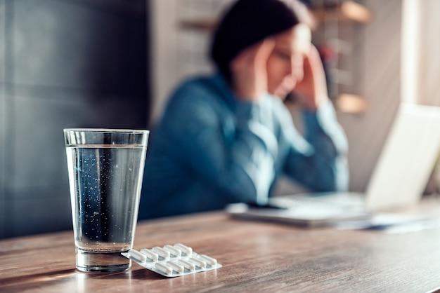 Donna con mal di testa e capsule con bicchiere d'acqua su una scrivania