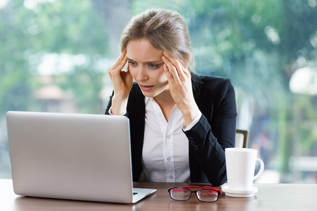 Donna con mal di testa guardando un computer portatile