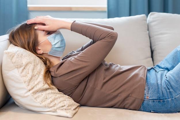 Donna con maschera in quarantena posa sul divano