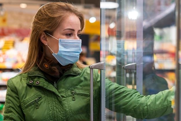 Donna con maschera protettiva prendendo prodotti dal frigorifero
