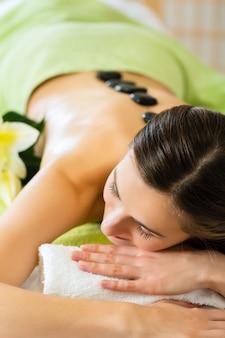 Donna con massaggio hot stone benessere