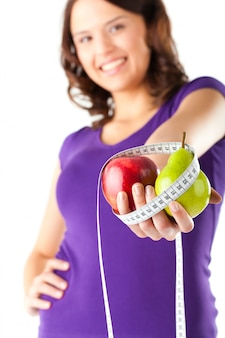 Donna con mela, pera e nastro di misurazione