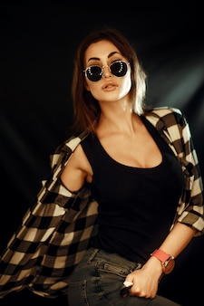 Donna con occhiali da sole e indossa la camicia a quadri