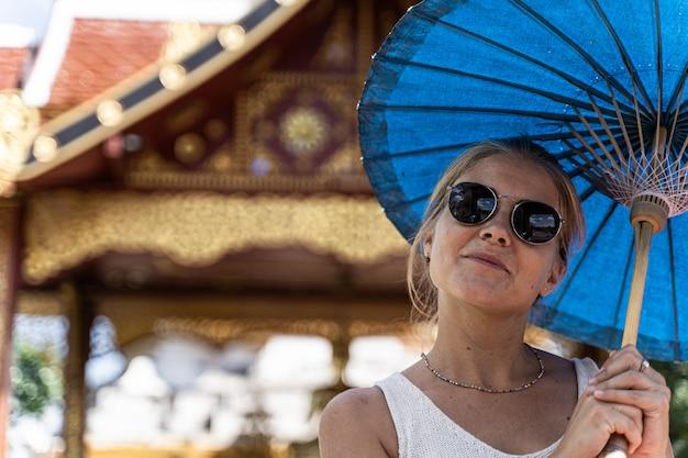 Donna con occhiali da sole e un ombrello blu tra le mani con una felice espressione di fronte a un tempio