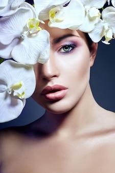 Donna con orchidea bianca vicino viso