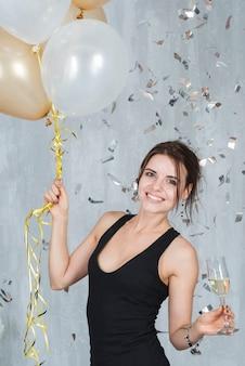 Donna con palloncini e champagne