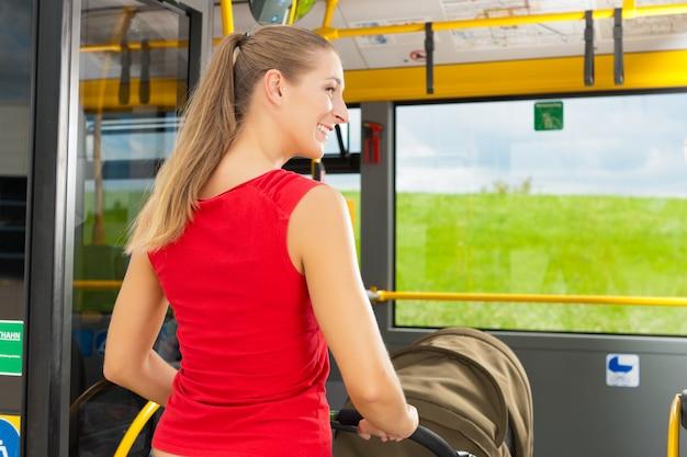Donna con passeggino salire su un autobus