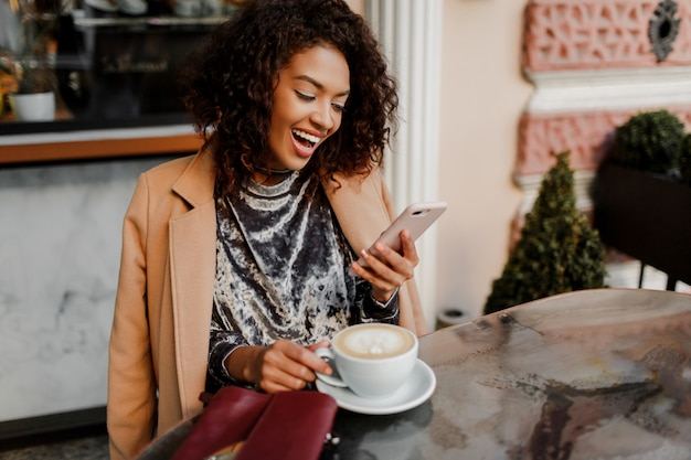 Donna con pelle nera e candido sorriso in chat per telefono e godendo la pausa caffè nella caffetteria
