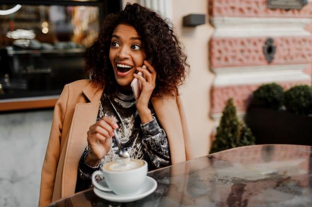 Donna con pelle nera e candido sorriso parlando al telefono e godendo