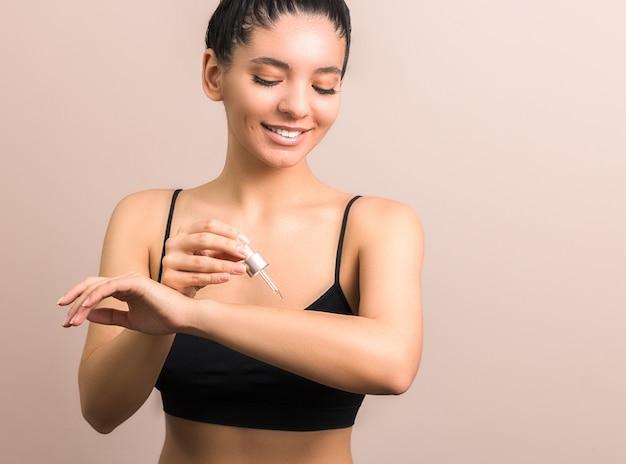 Donna con pelle pulita che applica olio per il corpo sul braccio