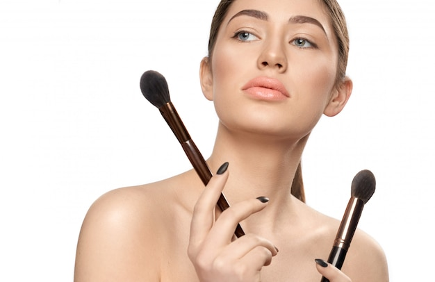 Donna con perfetto trucco nudo mantenendo spazzole per il trucco