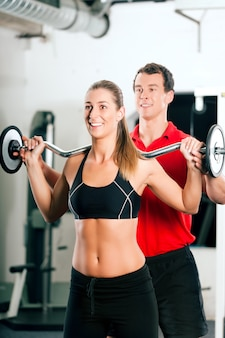 Donna con personal trainer in palestra