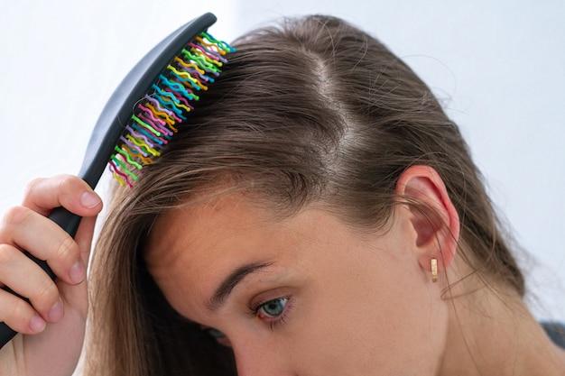 Donna con pettine che ha un problema di capelli e che soffre di perdita di capelli
