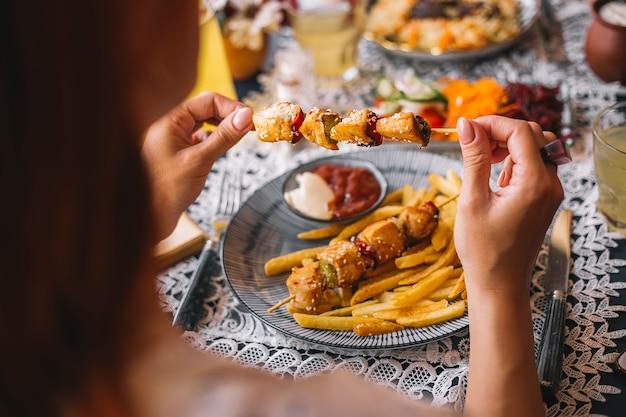 Donna con pezzi di pollo su spiedini cosparsi di sesamo