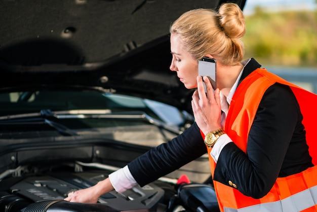 Donna con problemi al motore dell'automobile che chiama servizio di riparazione