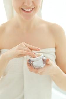 Donna con prodotti cosmetici e asciugamano sulla sua testa dopo la doccia