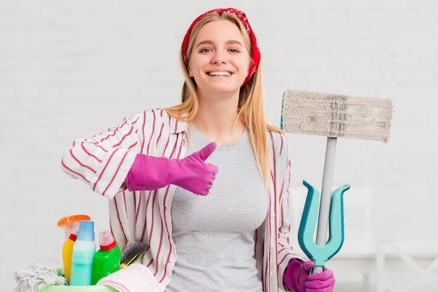 Donna con prodotti per la pulizia che mostra segno giusto