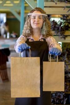 Donna con protezione per il viso al servizio dei clienti