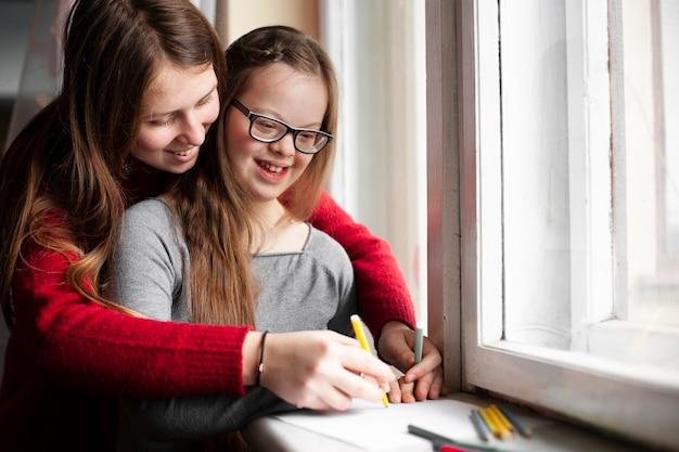 Donna con ragazza felice con il disegno di sindrome di down