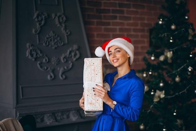 Donna con regali e in piedi davanti all'albero di natale