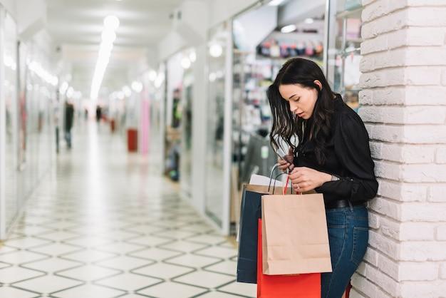 Donna con sacchetti di carta nel centro commerciale moderno