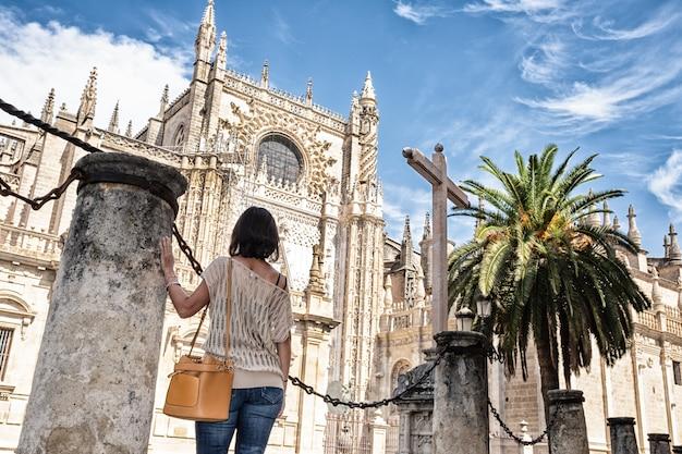 Donna con schiena contro una colonna guardando la cattedrale di siviglia