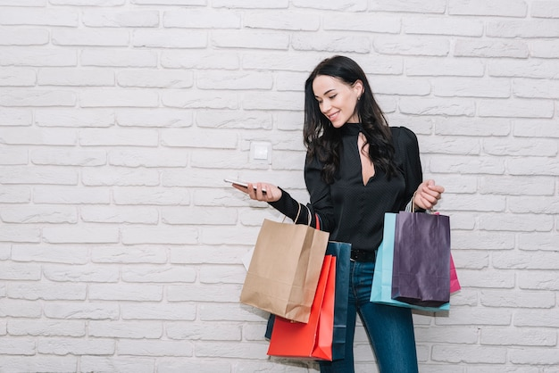 Donna con smartphone che tiene i sacchetti colorati