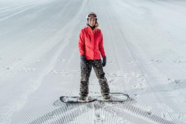 Donna con snowboard sulla pista da sci. equitazione serale