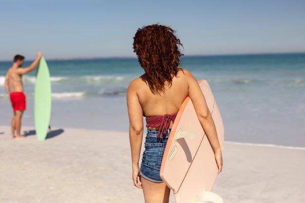 Donna con tavola da surf in piedi sulla spiaggia al sole