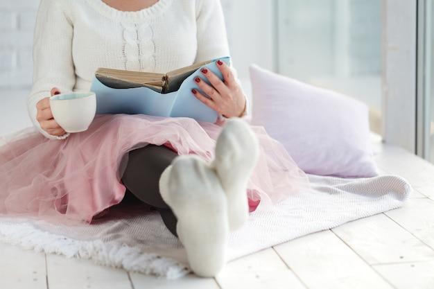 Donna con tazza di tè riposo scozzese, piede con calzini bianchi