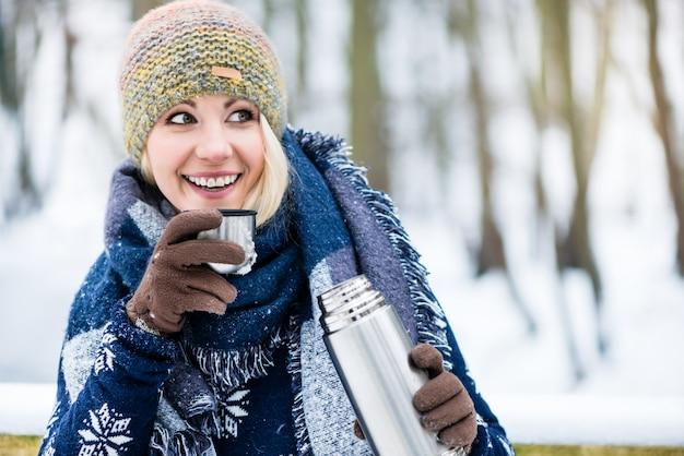 Donna con tè caldo o caffè su un'escursione invernale