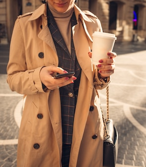 Donna con telefono e caffè al quadrato della fontana