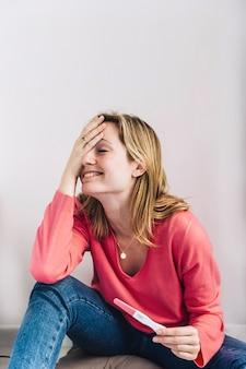 Donna con test di gravidanza e mano davanti alla faccia