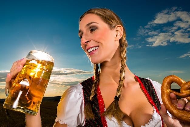 Donna con tracht, birra e pretzel in baviera