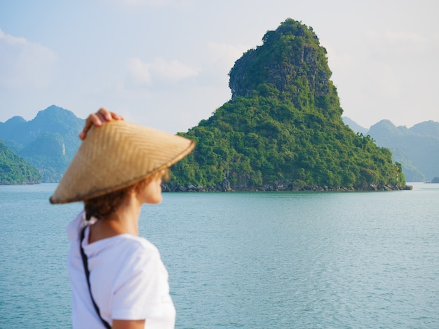 Donna con tradizionale guardando vista unica della baia di halong, vietnam. turista che viaggiano in crociera tra i pinnacoli di roccia di ha long bay nel mare. signora caucasica divertirsi in vacanza al famoso punto di riferimento.