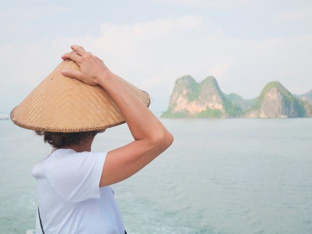 Donna con tradizionale guardando vista unica della baia di halong, vietnam.