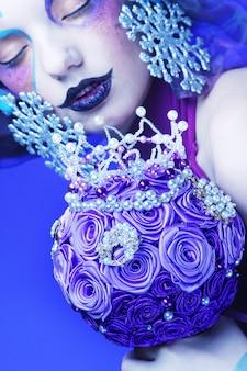 Donna con trucco creativo che tiene un mazzo di gioielli