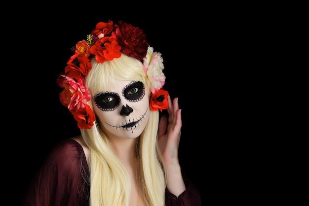 Donna con trucco del cranio dello zucchero e capelli biondi isolati su fondo nero. giorno della morte. halloween.