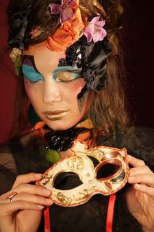 Donna con trucco luminoso con la maschera di carnevale