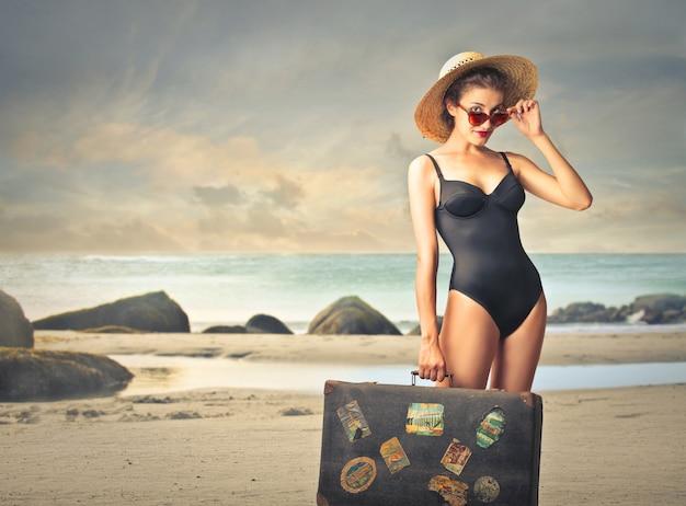 Donna con un bagaglio sulla spiaggia