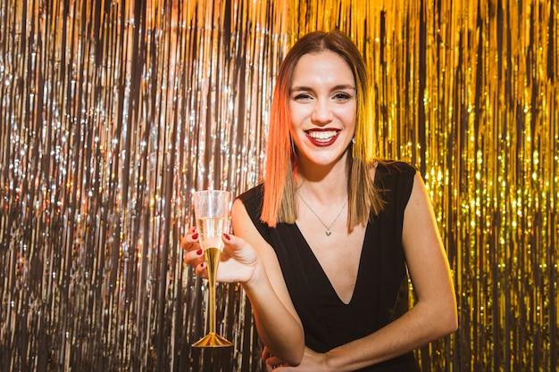 Donna con un bicchiere di champagne al partito di nuovo anno