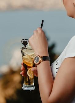 Donna con un bicchiere di cokcktail con fette di limone.