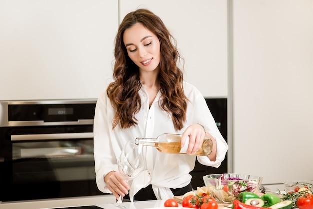 Donna con un bicchiere e una bottiglia di vino bianco nella cucina della cucina