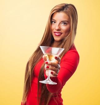 Donna con un bicchiere in uno sfondo giallo