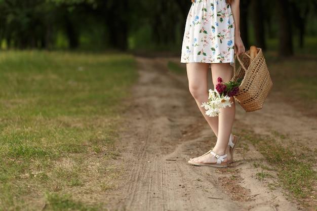 Donna con un cestino di vimini e fiori su una strada campestre.