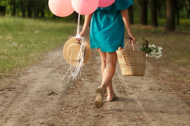 Donna con un cesto di vimini, cappello, palloncini rosa e fiori che camminano su una strada di campagna.