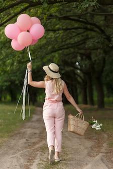 Donna con un cesto di vimini, cappello, palloncini rosa e fiori che camminano su una strada di campagna