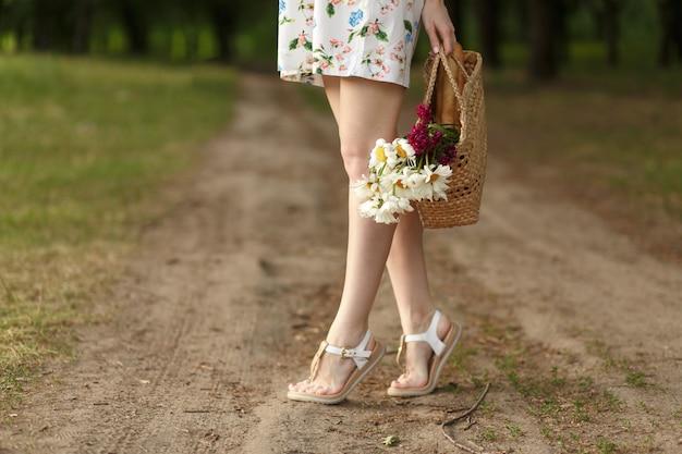 Donna con un cesto di vimini e fiori su una strada di campagna
